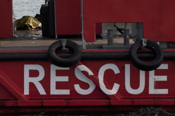 A covered body lies on a rescue boat, after two vessels collided in Hong Kong